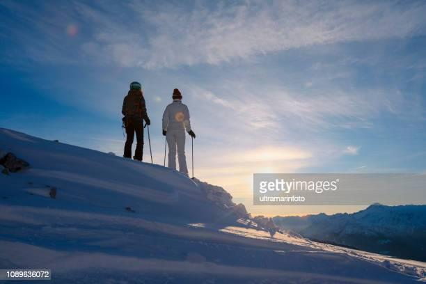 スキーの友人。日当たりの良いスキー場、イタリアの日没のドロミテ山でスキー雪のスキーヤー。 - スキー旅行 ストックフォトと画像