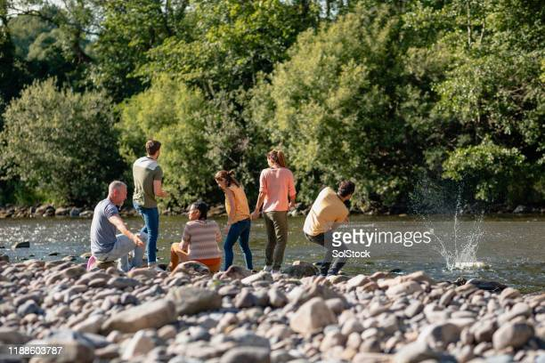 friends skimming stones - river stock pictures, royalty-free photos & images