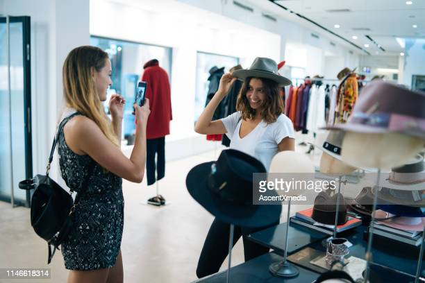 friends smile at each other while trying on outfits - only young women stock pictures, royalty-free photos & images