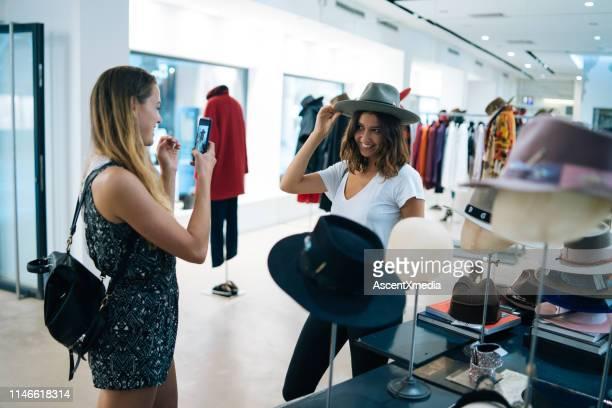 les amis sourient les uns aux autres tout en essayant sur des tenues - seulement des jeunes femmes photos et images de collection