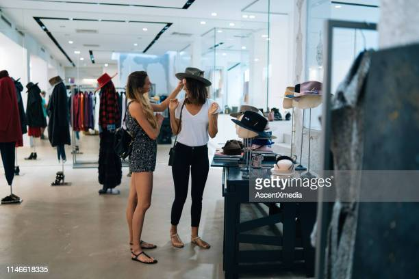 friends smile at each other while trying on outfits - fashion collection stock pictures, royalty-free photos & images