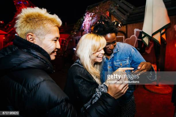 Friends Smiling And Laughing At Pictures While On Night Out Together