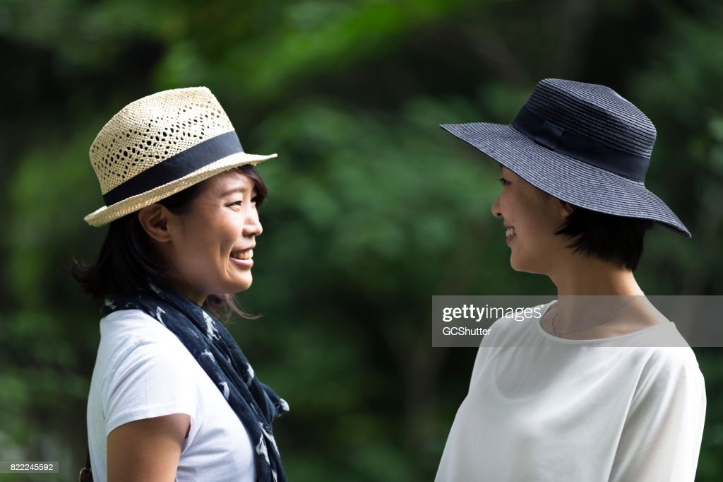 Friends smiling as they look at each other sharing a silent joke : Stock Photo