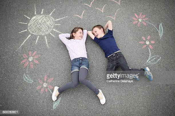 2 friends smiling laying on a decorated road - hot pants stock pictures, royalty-free photos & images