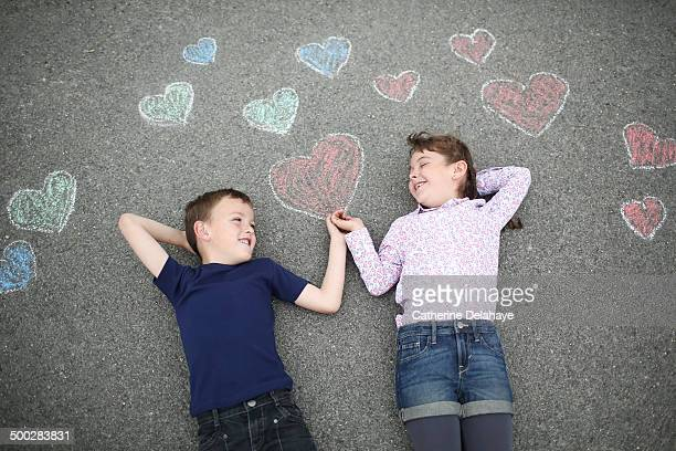 2 friends smiling laying on a decorated road