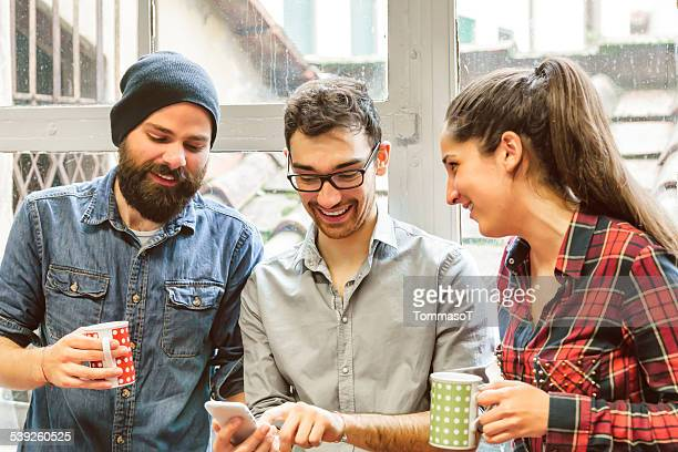 Friends smiling looking at smartphone in front of a window