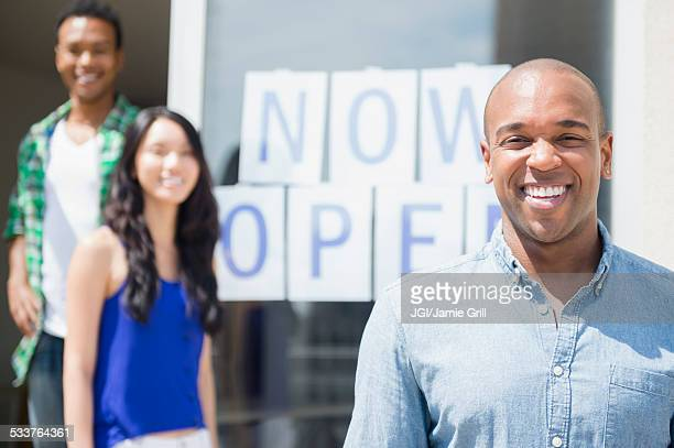 Friends smiling together by newly open storefront