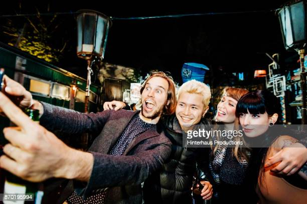 Friends Smiling While Taking Selfie Together At Open Air Nightclub