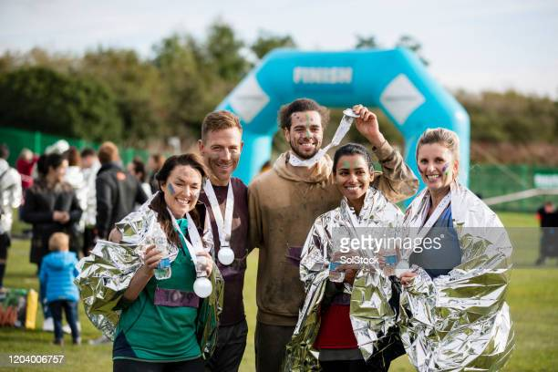 friends smiling with medals after charity run - medallist stock pictures, royalty-free photos & images