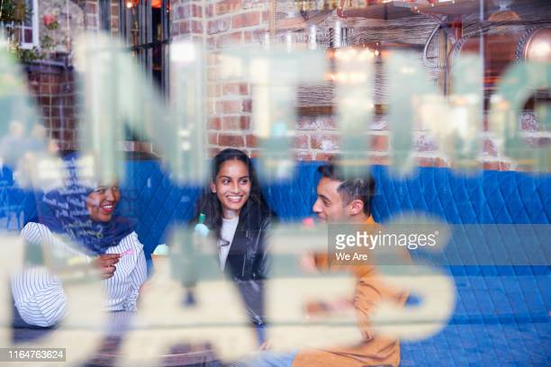 friends socialising in a cafe - restaurant stock pictures, royalty-free photos & images