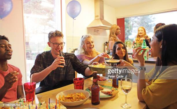 friends socializing at house party - person in education stock pictures, royalty-free photos & images