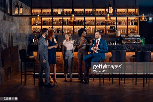 friends socializing at the counter in a bar - well dressed stock pictures, royalty-free photos & images
