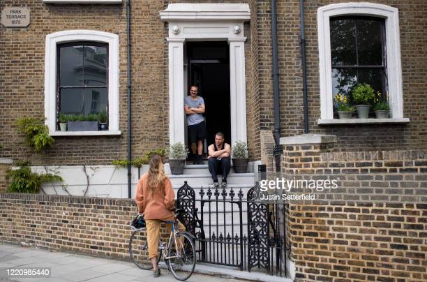 Friends speak from a social distance of 2 meters outside a house in East London on April 25, 2020 in London, England. The British government has...