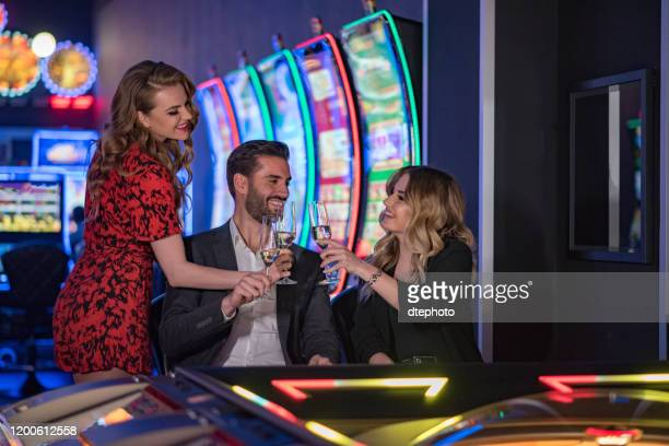 friends spednig time together at casino - gambling table stock pictures, royalty-free photos & images