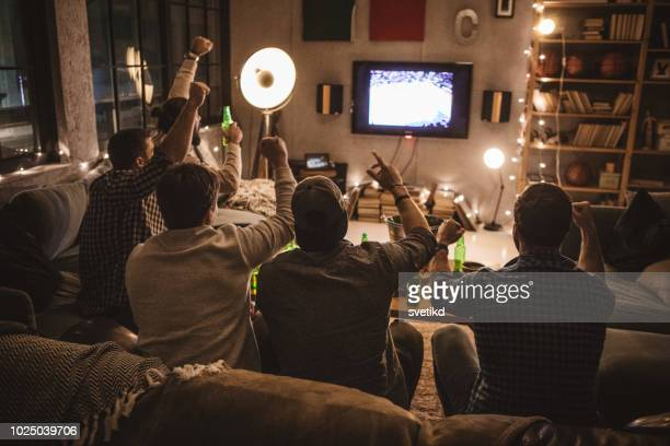 friends spend weekend together watching tv - football stock pictures, royalty-free photos & images