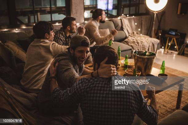 friends spend weekend together watching tv - american football sport stock pictures, royalty-free photos & images