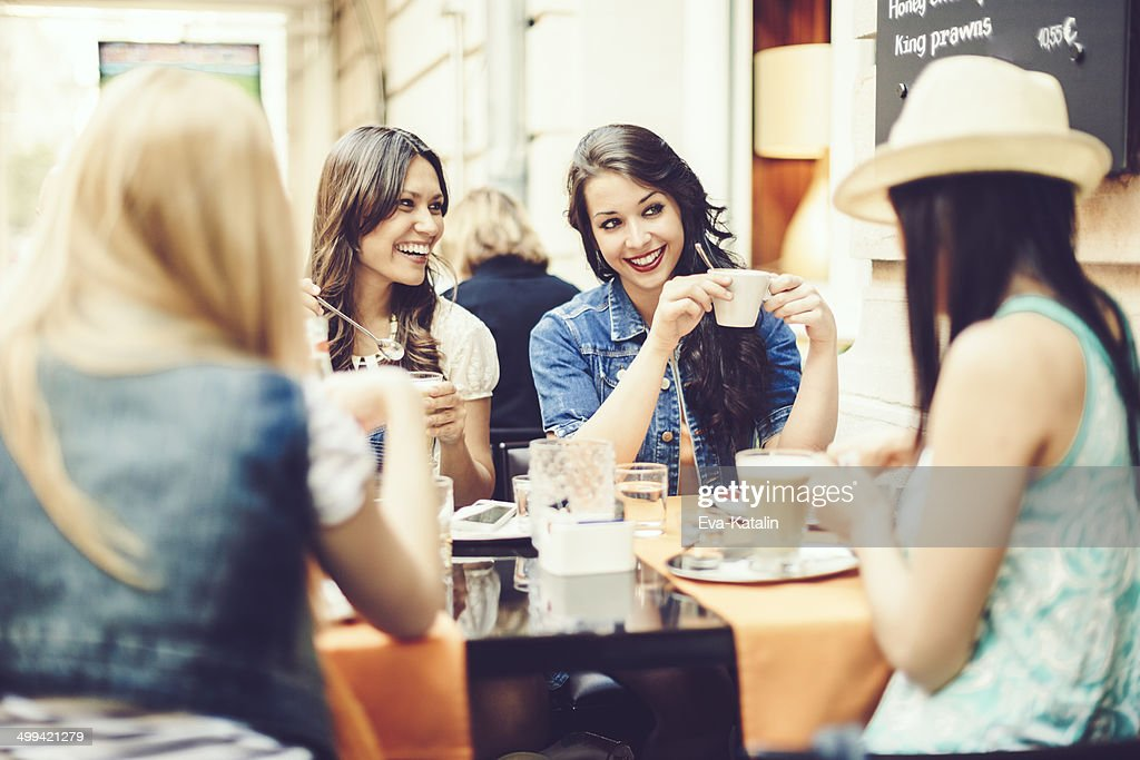 Friends spending time together in a coffee shop : Stock Photo