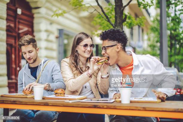 friends spending time together in the city - man eating woman out stock photos and pictures