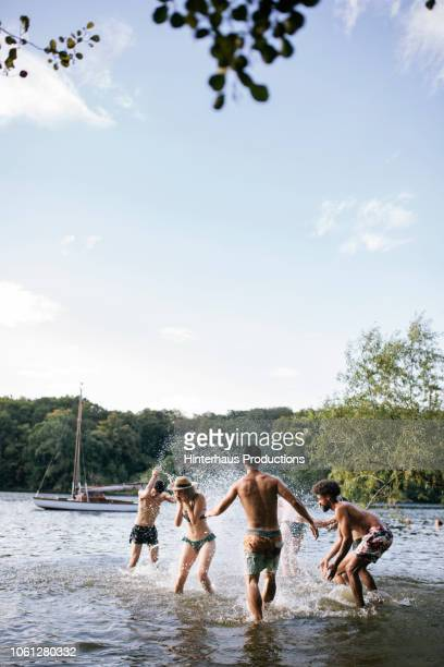 friends splashing around in lake together - vertical stock pictures, royalty-free photos & images