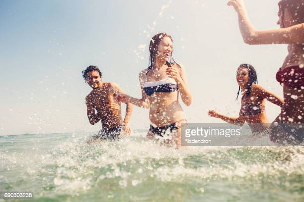 Friends splashing each other with water