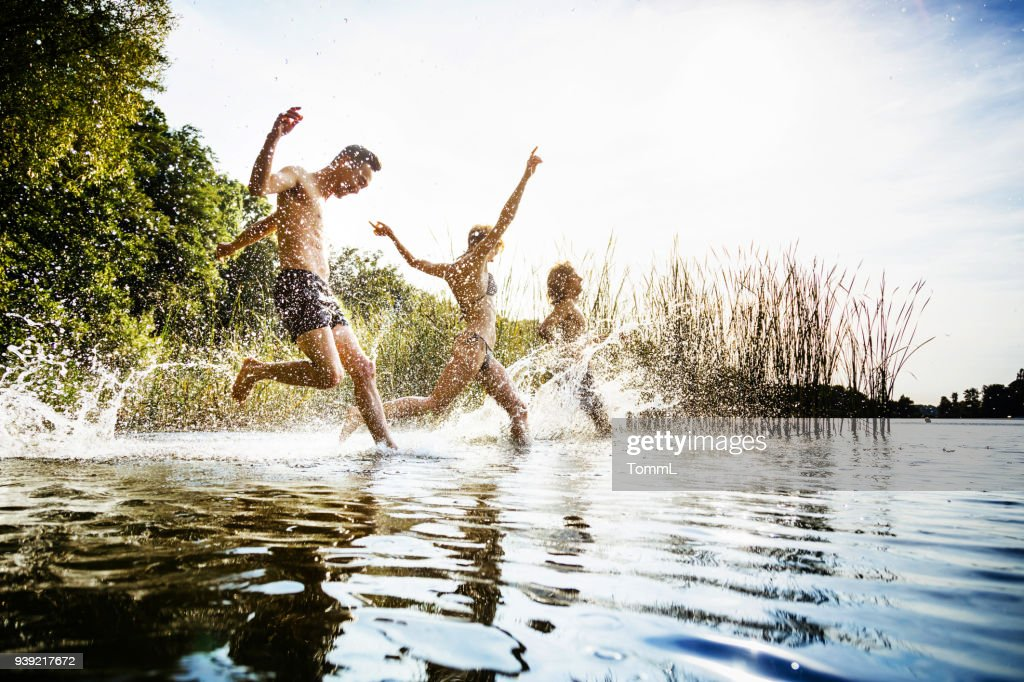 Friends Splashing In Water At Lake Together : Stock Photo