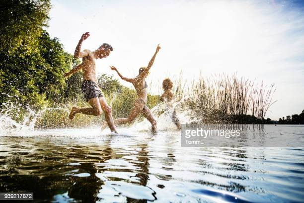 friends splashing in water at lake together - jumping stock pictures, royalty-free photos & images