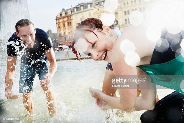 Friends splashing in water of fountain