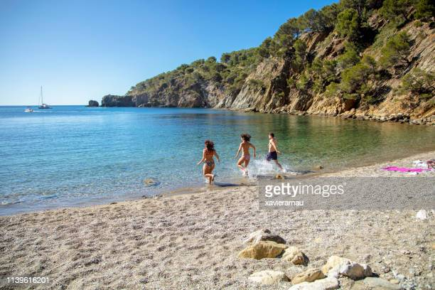 friends splashing water while running on shore - girona stock photos and pictures