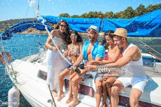 Friends splashing with champagne on yacht