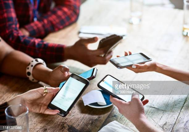 friends splitting bill using contactless payment on smartphones - friendship stock pictures, royalty-free photos & images