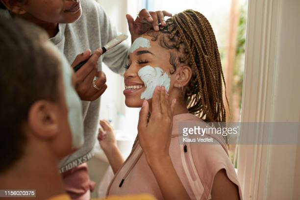 friends spreading cream on woman's face - vanity stock pictures, royalty-free photos & images