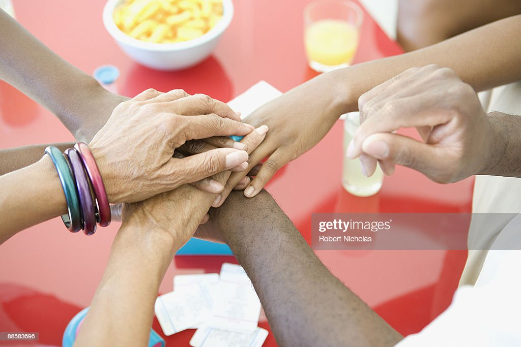 Friends stacking hands : Stock Photo