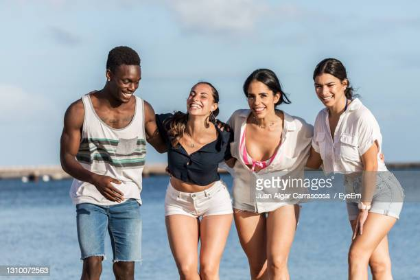 friends standing against sea - lanzarote stock pictures, royalty-free photos & images