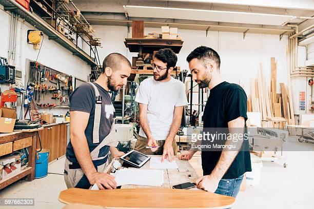Friends standing around workbench in carpentry workshop talking
