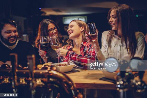 friends standing at the bar counter - happy hour stock pictures, royalty-free photos & images
