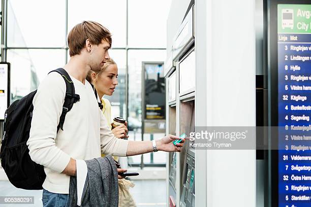 Friends standing by ATM at railroad station
