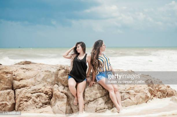 friends standing by rocks at beach against sky - ruben vardanyan stock pictures, royalty-free photos & images