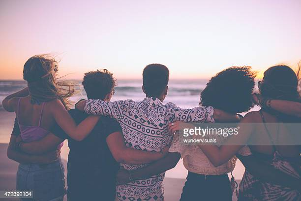 Friends standing in a row watching the ocean at sunset