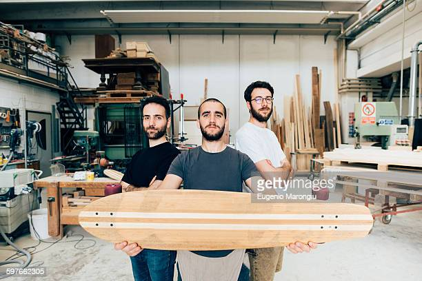 Friends standing in carpentry workshop holding skateboard looking at camera