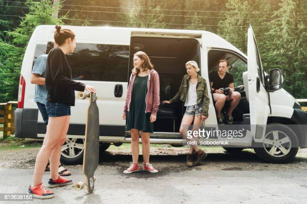 Friends standing near the van in the forest