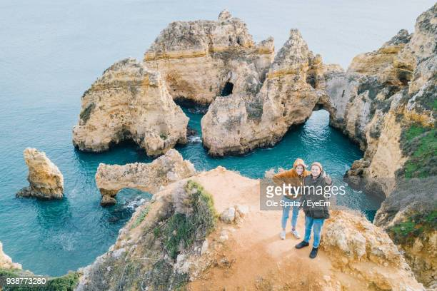 Friends Standing On Cliff Against Sea