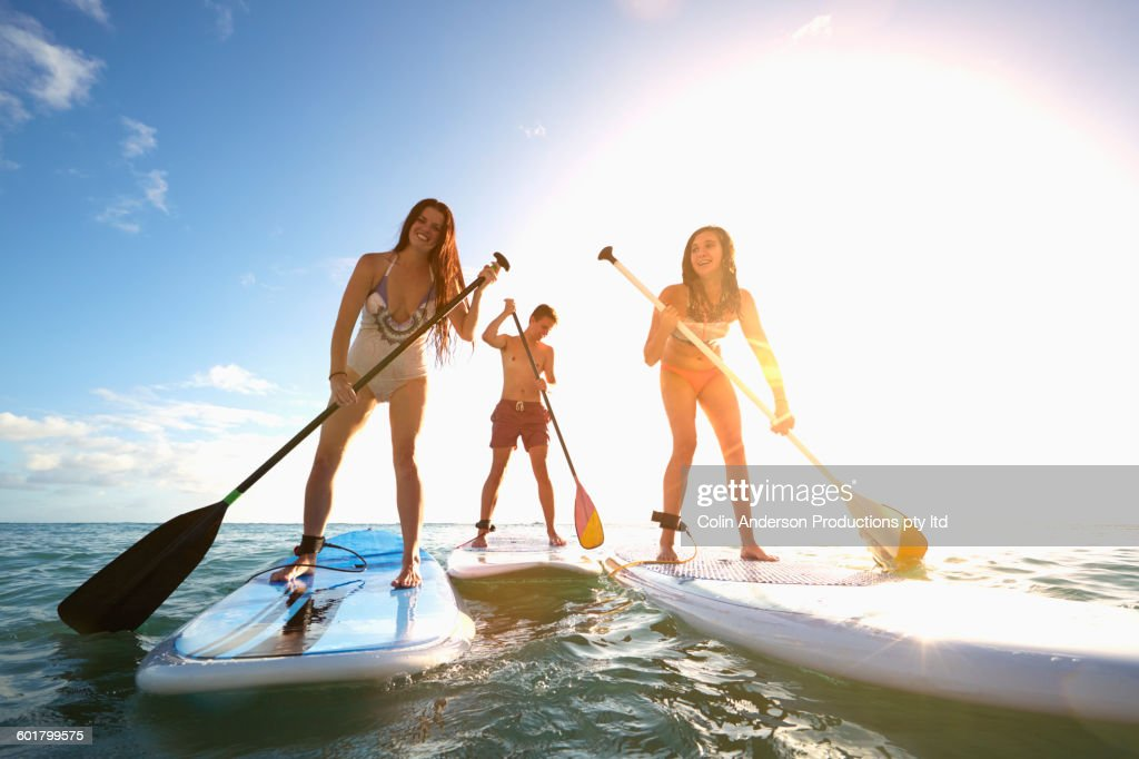 Friends standing on paddle boards in ocean : Stock Photo