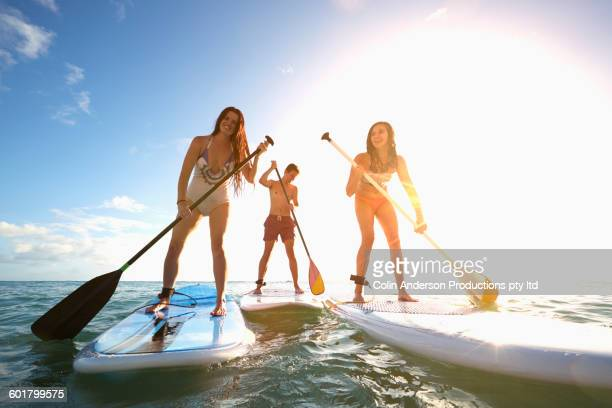 friends standing on paddle boards in ocean - wassersport stock-fotos und bilder