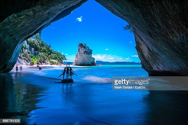 Friends Standing On Rock In Arch Cave At Beach