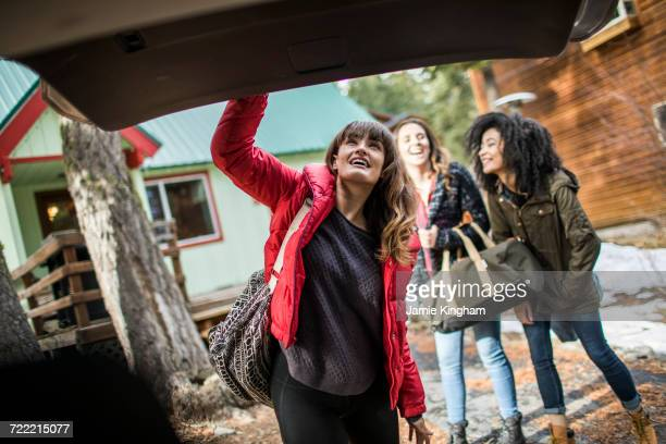 Friends standing outside cabin, young woman closing boot of car