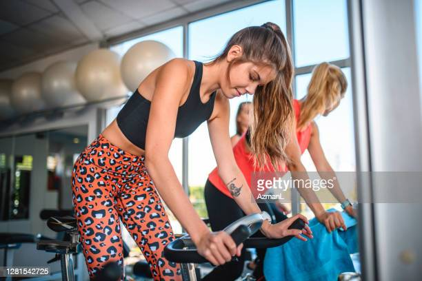 friends standing while riding stationary bicycle at gym - peloton stock pictures, royalty-free photos & images