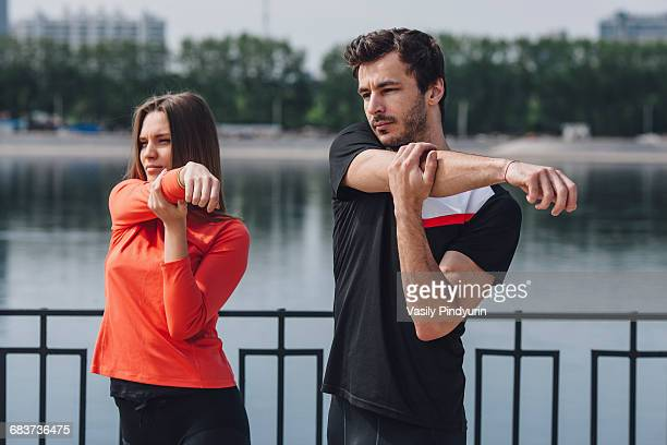 Friends stretching arms by railing next to lake