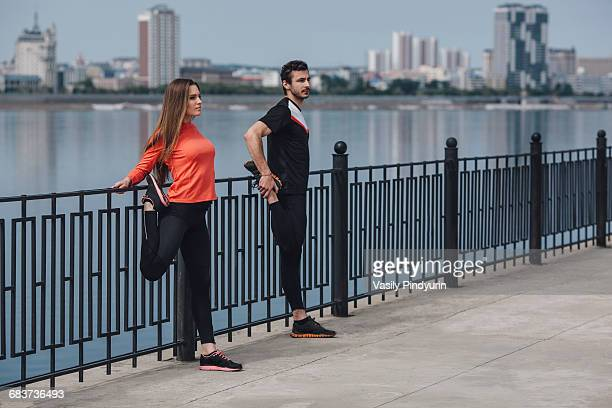 Friends stretching legs while standing on promenade next to lake