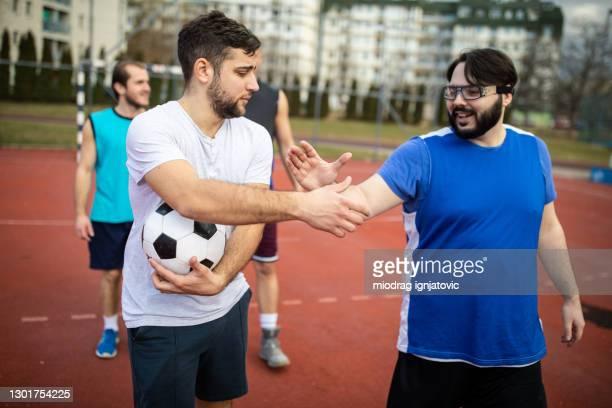 amici che si sostengono a vicenda prima dell'inizio della partita di calcio - fat soccer players foto e immagini stock