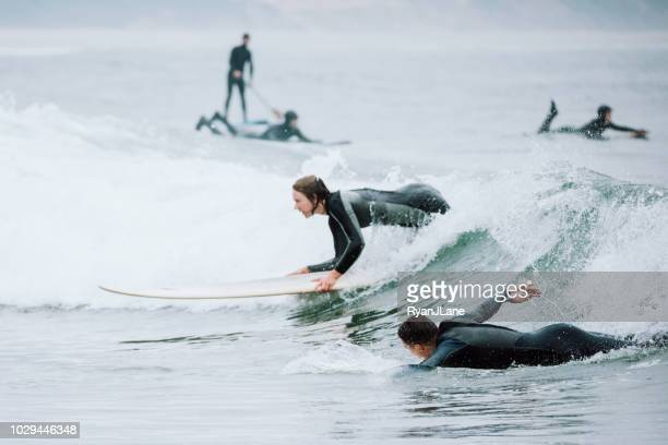 friends surfing at oregon coast - oregon coast stock pictures, royalty-free photos & images